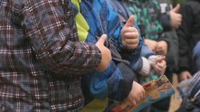 Los niños que se colocan en el parque aumentan sus pulgares para arriba almacen de metraje de vídeo
