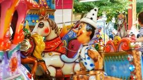 los niños que se divierten en el carrusel juegan la atracción en el funfair metrajes