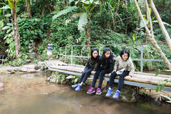 Los niños que se sientan en el puente de madera por la cala de la montaña miran pescados Fotografía de archivo