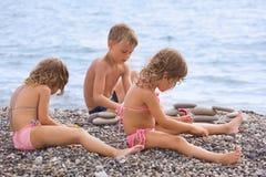 Los niños que se sientan en la playa pedregosa, crean la pirámide Imágenes de archivo libres de regalías