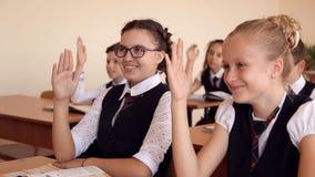 Los niños que se sientan en sus escritorios, algunos de los estudiantes de ellos aumentan sus manos metrajes