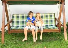 Los niños que se sientan en un jardín balancean con los perros Imagenes de archivo