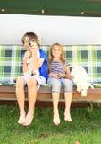 Los niños que se sientan en un jardín balancean con los perros Fotografía de archivo