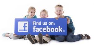 Los niños que sostienen Facebook nos encuentran muestra Foto de archivo