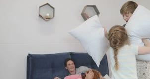 Los niños que tienen lucha de almohadas en padres acuestan, diversión feliz de la familia en la risa del dormitorio metrajes