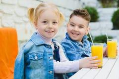 Los niños que tienen niños sanos del desayuno que beben los jugos y se divierten imagenes de archivo