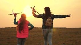 Los niños quieren hacer piloto y astronauta Las muchachas felices corren con el avi?n del juguete en la puesta del sol en campo r almacen de metraje de vídeo