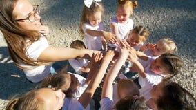 Los niños realizan deportes que saludan con sus manos en el patio del fútbol de la yarda, visión superior, a cámara lenta almacen de metraje de vídeo