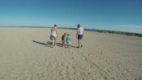Los niños recogen conchas marinas cerca de la costa metrajes
