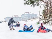 Los niños resbalan en nieve con la caja plástica en Estambul Fotos de archivo libres de regalías