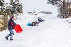 Los niños resbalan en nieve con la caja plástica en Estambul Fotografía de archivo libre de regalías