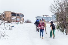 Los niños resbalan en nieve en estilo de la escuela vieja con madera dura Imagen de archivo
