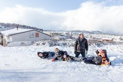 Los niños resbalan en nieve en estilo de la escuela vieja con madera dura Imágenes de archivo libres de regalías