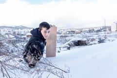 Los niños resbalan en nieve en estilo de la escuela vieja con madera dura Fotos de archivo