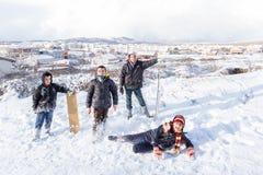 Los niños resbalan en nieve en estilo de la escuela vieja con madera dura Fotografía de archivo