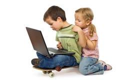 Los niños rivalizan para usar la computadora portátil Foto de archivo