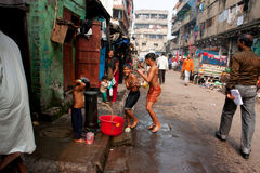 Los niños saltan en la calle en el tiempo del baño fotografía de archivo