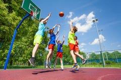 Los niños saltan para la bola de vuelo durante baloncesto fotos de archivo