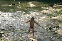 Los niños se bañan en un río de la montaña imagen de archivo