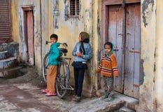 Los niños se divierten con la bicicleta en un patio de la casa pobre Imagen de archivo libre de regalías