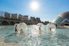 Los niños se divierten dentro de baloons grandes del aire en una piscina en la ciudad o Foto de archivo libre de regalías