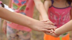 Los niños se divierten mucho en el verano en el césped en el parque, ríen y juegan la diversión almacen de metraje de vídeo