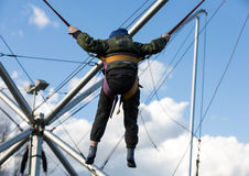 Los niños se divierten que salta en el trampolín del amortiguador auxiliar asegurado con las gomas Foto de archivo