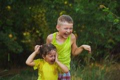 Los niños se están divirtiendo debajo de la lluvia del verano Imagen de archivo