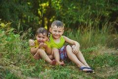 Los niños se están divirtiendo debajo de la lluvia del verano Foto de archivo