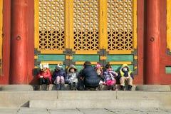 Los niños se están sentando delante de un shrime para conseguir calientes Imagen de archivo