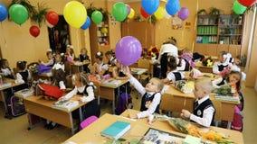 Los niños se están sentando en los escritorios en la sala de clase en el primer día de escuela almacen de metraje de vídeo