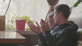 Los niños se están sentando en un café que juega a juegos en el vídeo de la cámara lenta del smartphone medios sociales de las ad metrajes