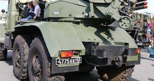 Los niños se están sentando en vehículos de combate Objeto expuesto del museo del equipo militar almacen de video