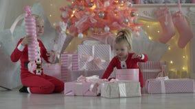 Los niños se sientan bajo rosa del árbol de navidad almacen de metraje de vídeo