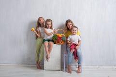 Los niños se sientan con la fruta sana de la consumición de las verduras frescas foto de archivo
