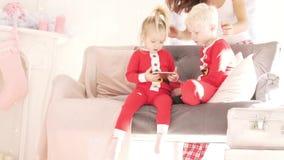 Los niños se sientan en casa en el sofá almacen de metraje de vídeo