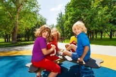 Los niños se sientan en el carrusel y la sonrisa del patio Fotos de archivo libres de regalías