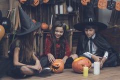 Los niños se sientan en el piso a piernas cruzadas delante de las calabazas talladas para un partido de Halloween Imagen de archivo libre de regalías
