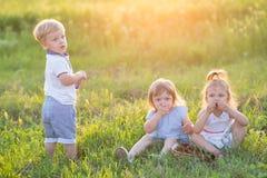Los niños se sientan en la hierba Fotografía de archivo libre de regalías