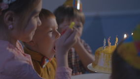 Los niños se sientan en la tabla roja con la torta Grupo feliz de niños en la fiesta de cumpleaños almacen de video