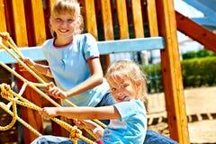 Los niños se trasladan hacia fuera a la diapositiva en patio Imágenes de archivo libres de regalías