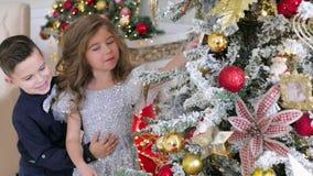 Los niños se vistieron en ropa elegante adornan un árbol de rosas Humor festivo almacen de metraje de vídeo