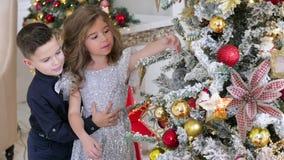 Los niños se vistieron en ropa elegante adornan un árbol de rosas Humor festivo metrajes