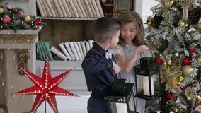 Los niños se vistieron en ropa elegante adornan un árbol de rosas sostenga las linternas almacen de metraje de vídeo