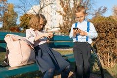 Los niños serios elegantes muchacho y muchacha están mirando en smartphones En un banco con las mochilas de la escuela, parque so imagen de archivo