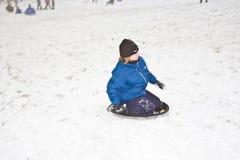 Los niños sledding abajo de la colina en nieve Fotos de archivo libres de regalías