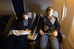 Los niños son relajantes y durmientes en un avión en cl del negocio Foto de archivo libre de regalías