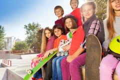 Los niños sonrientes con los monopatines se sientan juntos Foto de archivo libre de regalías