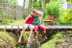 Los niños sonrientes felices se sientan en el puente en el abarcamiento uno otro de The Creek en un jardín Foto de archivo libre de regalías