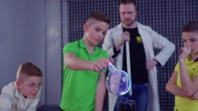 Los niños sostienen la esfera de cristal sobre la bobina de Tesla metrajes